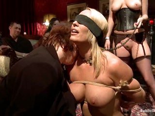 Pliant slave Mellanie Monroe is put on display at a party.