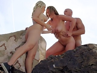Three girls are around a dude, licking and sucking his large dick